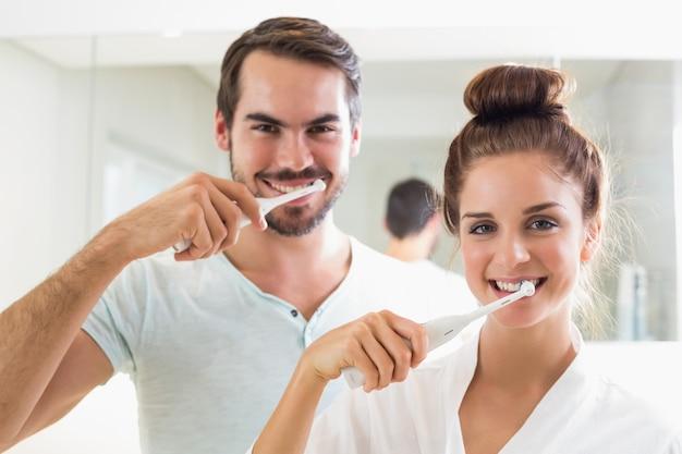 Junges paar, das ihre zähne putzt