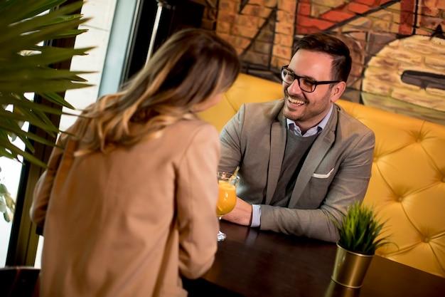Junges paar, das im café sitzt und orangensaft trinkt