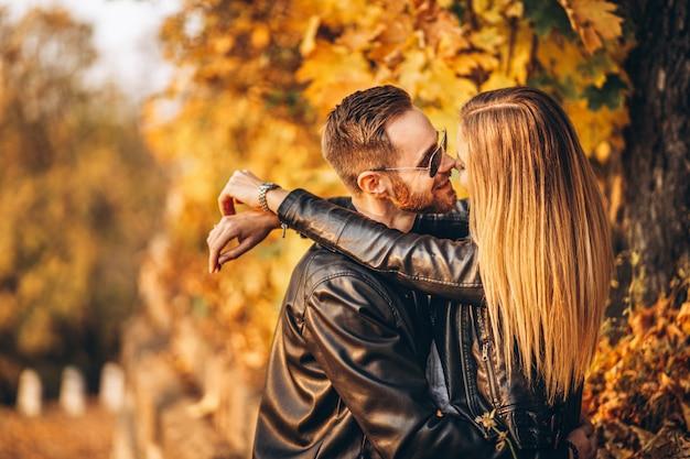 Junges paar, das im herbstlichen park küsst. ein mann hob seine frau in die arme
