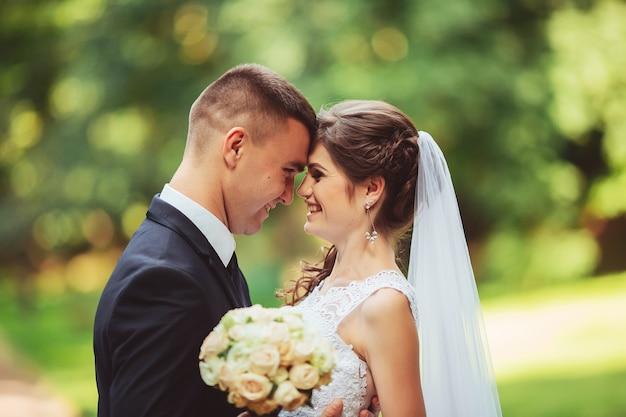 Junges paar, das im hochzeitskleid küsst. braut, die blumenstrauß hält