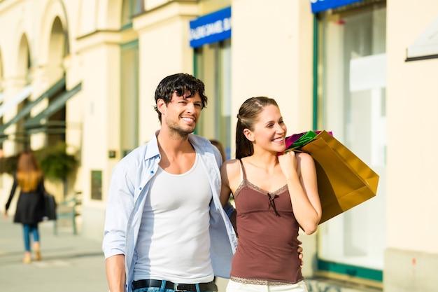 Junges paar, das im inneren mit einkaufstaschen einkauft, die geld ausgeben