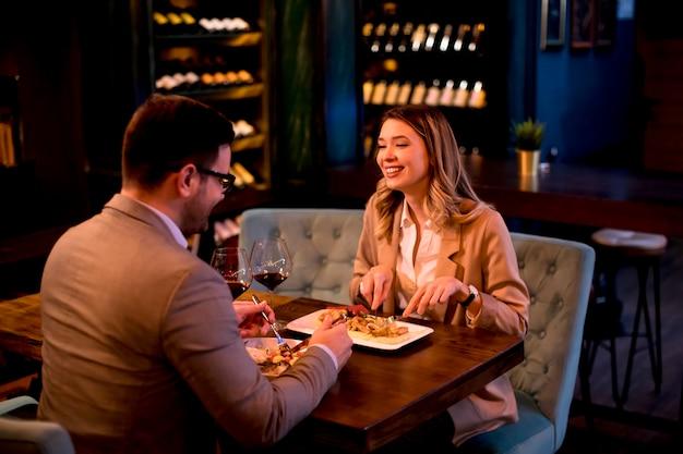 Junges paar, das im restaurant zu abend isst und rotwein trinkt