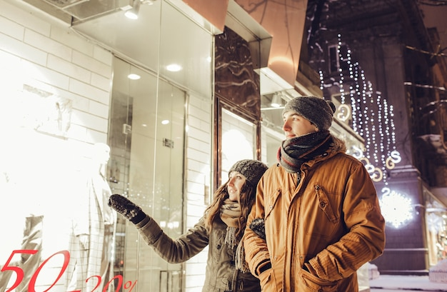Junges paar, das im stadtzentrum geht und nachts schaufensterbummel macht.