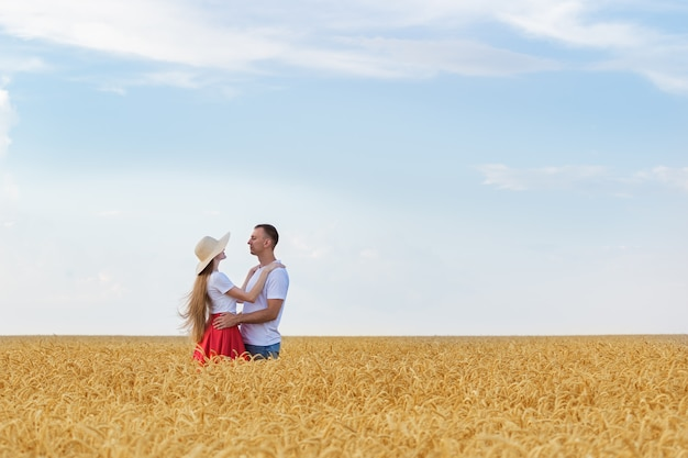 Junges paar, das im weizenfeld am sonnigen sommertag umarmt. glückliches paar verliebt im freien
