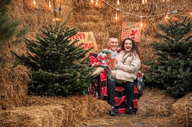 Junges paar, das in den weihnachtsgarten nahe dem weihnachtsbaum geht