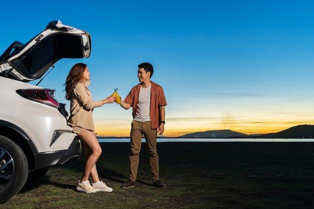 Junges paar, das in der nähe eines autos steht und bei sonnenuntergang im feld genießt?