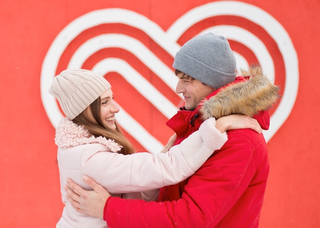 Junges paar, das in der stadt nahe dem großen herzen an der wand umarmt. sich gegenseitig ansehen. valentinstag. hochwertiges foto