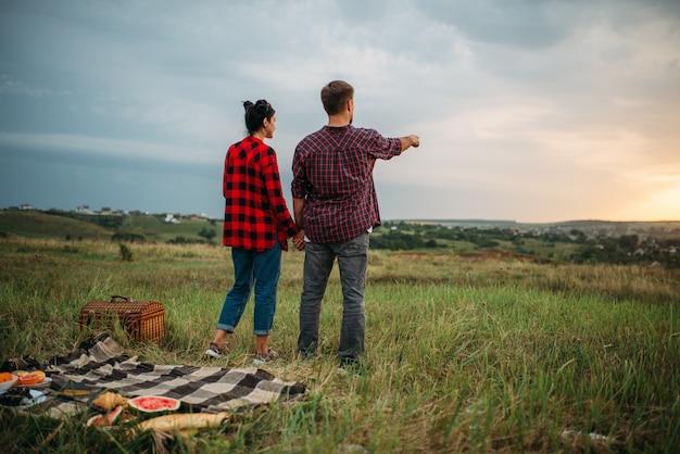 Junges paar, das in die ferne schaut, picknick auf dem feld. romantisches junket, mann und frau beim abendessen im freien