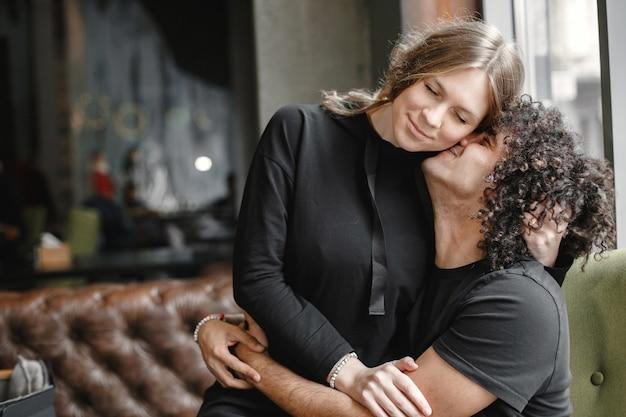 Junges paar, das in einem café umarmt.