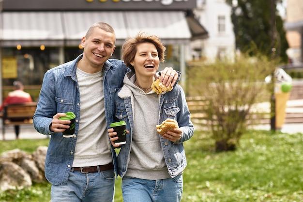 Junges paar, das kaffee beim gehen durch die stadt trinkt