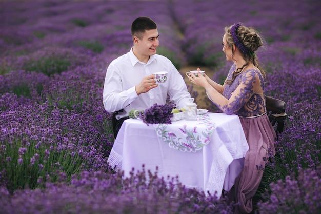 Junges paar, das kaffee in einem lavendelfeld trinkt