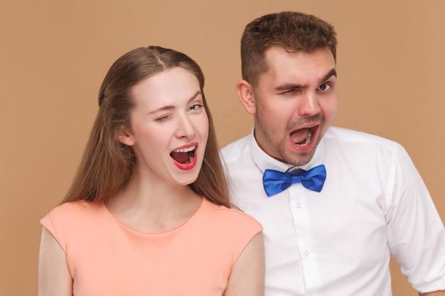 Junges paar, das kamera mit offenem mund des lustigen gesichts und zwinkern betrachtet
