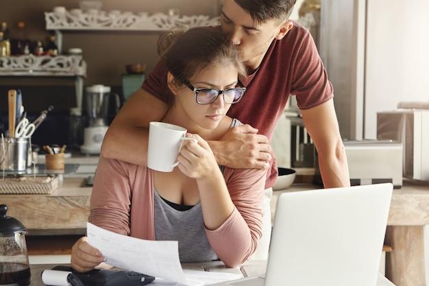 Junges paar, das kreditproblem in bank hat. unterstützender mann, der seine unglückliche frau auf ihrem kopf umarmt und küsst, während sie am küchentisch vor laptop sitzt