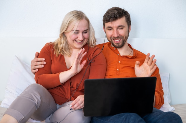 Junges paar, das laptop benutzt und ihre hände winkt