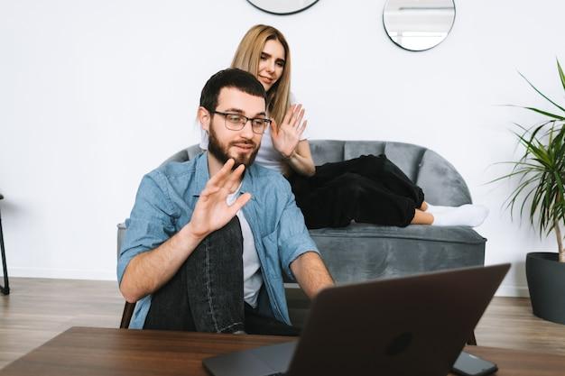 Junges paar, das laptop-computer verwendet, der laptop-bildschirm auf videoanruf und begrüßung mit winken im modernen wohnzimmer betrachtet.