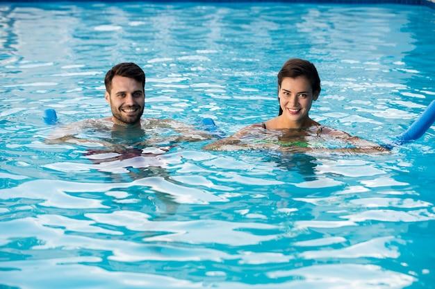 Junges paar, das mit aufblasbaren schläuchen im pool schwimmt