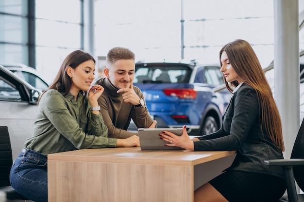Junges paar, das mit einem verkäufer in einem autohaus spricht