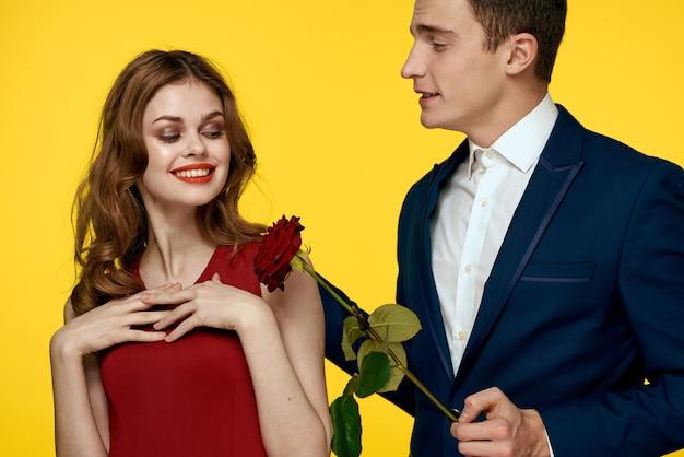 Junges paar, das mit einer rose aufwirft