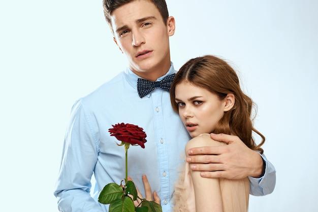 Junges paar, das mit rose aufwirft