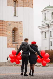 Junges paar, das mit roten luftballons geht
