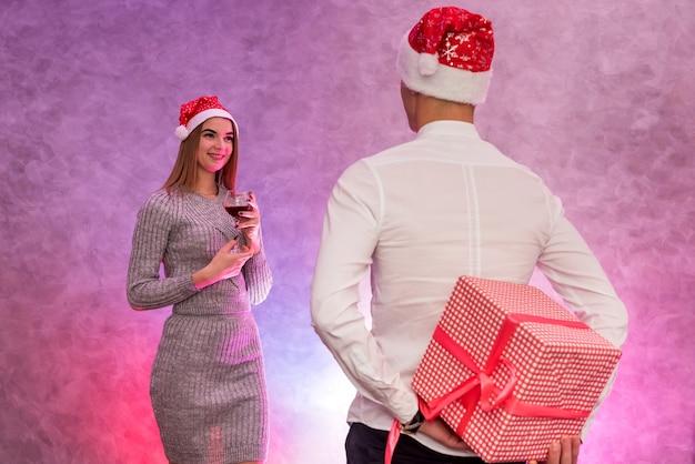 Junges paar, das mit weihnachtsgeschenken austauscht. weihnachts- und neujahrsfeier