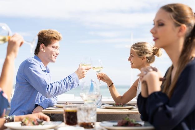 Junges paar, das mit weißwein vor dem meer in einer restaurantterrasse röstet