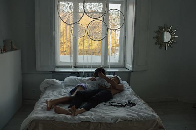 Junges paar, das morgens auf weichem weißem bett liegt und umarmt.
