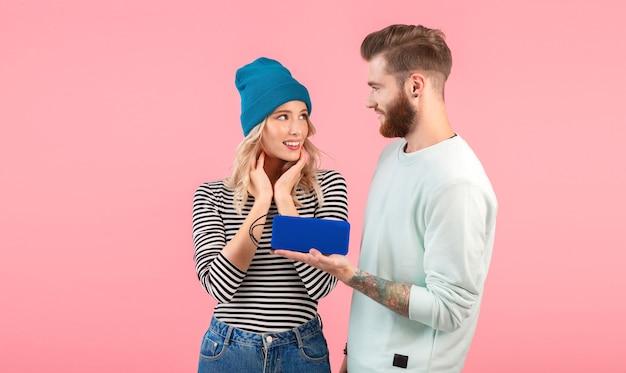 Junges paar, das musik auf drahtlosem lautsprecher hört, der kühles stilvolles outfit trägt, das lächelnd auf rosa aufwirft Kostenlose Fotos