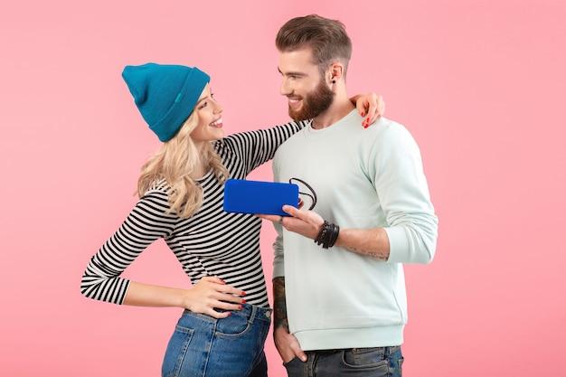 Junges paar, das musik auf drahtlosem lautsprecher hört, der kühles stilvolles outfit trägt, das lächelnd auf rosa aufwirft