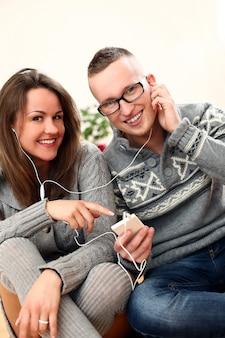Junges paar, das musik hört