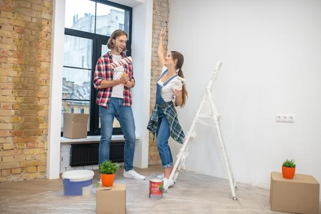 Junges paar, das n im leeren raum steht, bereit zu malen