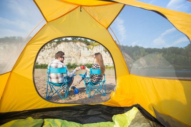 Junges paar, das nahe campingzelt ruht