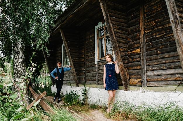 Junges paar, das nahe einem alten hölzernen stilvollen haus auf dem hintergrund der birke und der natur steht