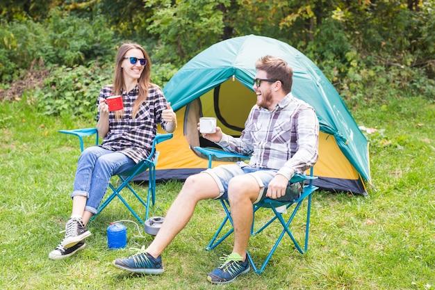 Junges paar, das nahe einem zelt sitzt