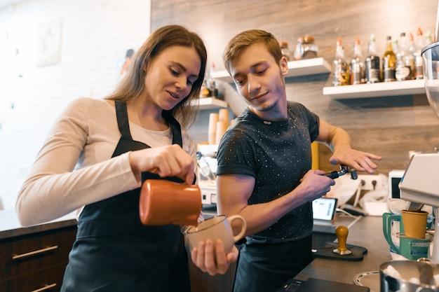Junges paar, das nahe kaffeemaschinen arbeitet und getränke macht