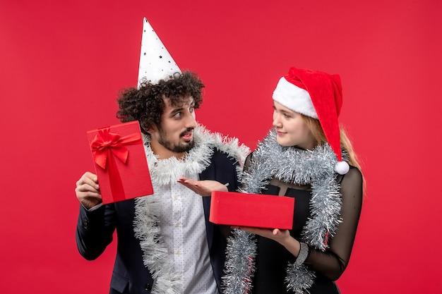 Junges paar, das neujahrsgeschenk-weihnachtsliebesfeier eröffnet