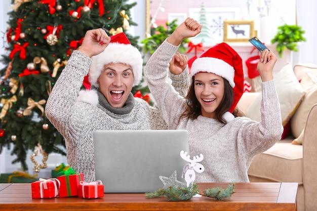 Junges paar, das online mit kreditkarte zu hause für weihnachten einkauft