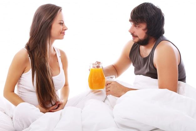 Junges paar, das orangensaft trinkt