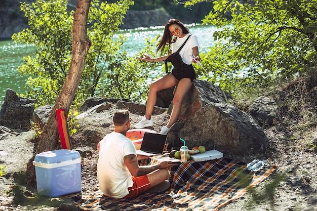 Junges paar, das picknick am flussufer im sonnigen tag hat.