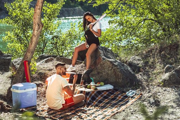 Junges paar, das picknick am flussufer im sonnigen tag hat