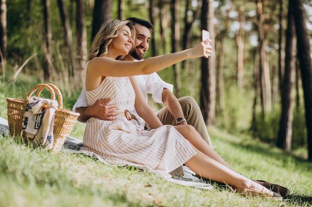 Junges paar, das picknick im wald hat