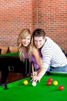 Junges paar, das pool spielt