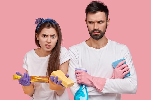 Junges paar, das reinigungsprodukte hält