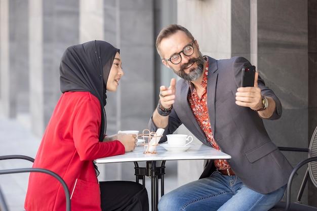 Junges paar, das romantisch im restaurant sitzt und fotos macht