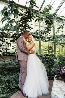 Junges paar, das romantische momente beim gehen im park genießt. stilvolle braut und bräutigam, die an ihrem hochzeitstag im park posieren und küssen. elegante braut im schönen weißen kleid, bräutigam im anzug.