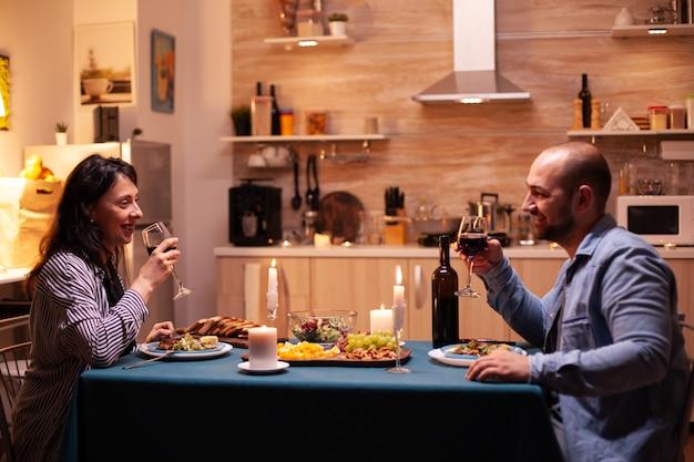 Junges paar, das romantische zeit beim abendessen hat. glückliches paar reden, am tisch im esszimmer sitzen, das essen genießen, ihr jubiläum zu hause mit romantischer zeit feiern.