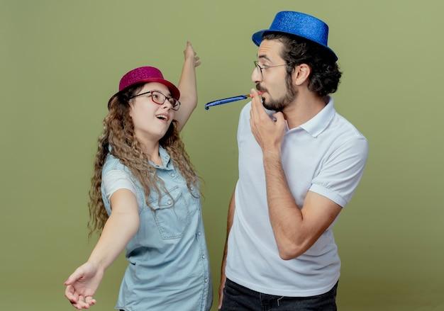 Junges paar, das rosa und blauen hutblick auf einander mädchen trägt, breitet hände aus und kerl bläst pfeife isoliert auf olivgrün