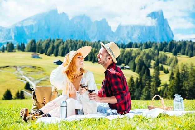 Junges paar, das rotwein trinkt, das auf dem landschaftsfeld sitzt?