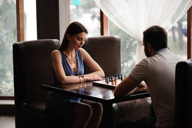 Junges paar, das schach im restaurant spielt