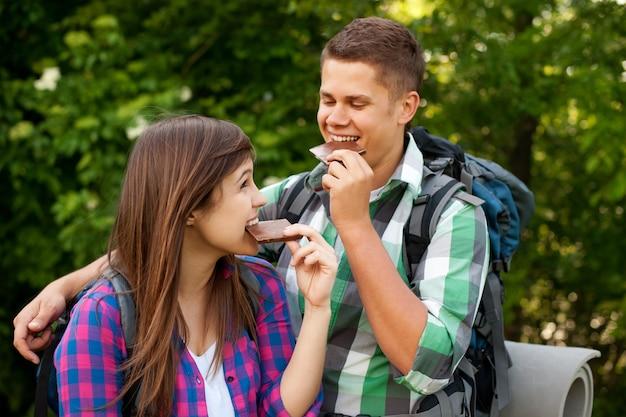 Junges paar, das schokolade im wald isst